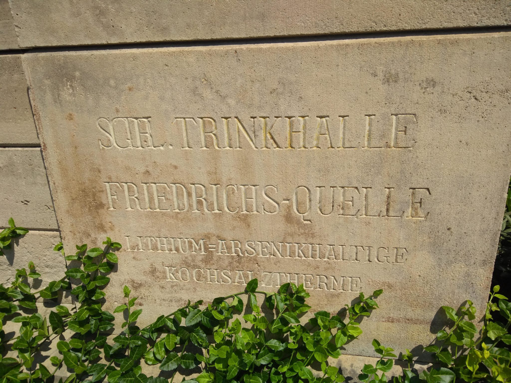 """An engraving on the side of the Trinkhalle that reads in German, """"""""Lithium- and Arsenic-containing saline thermal spa."""""""